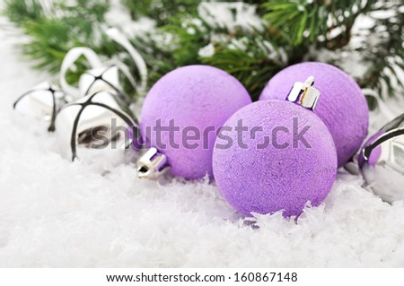 Pink christmas balls and fir branches with decorations on snow - stock photo