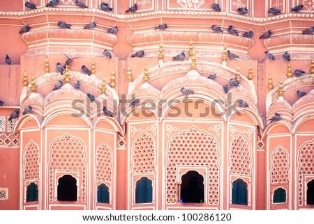 pink city Hawa Mahal palace wall with pigeons - stock photo