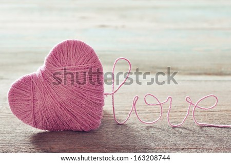 "Pink clew in shape of heart and word ""love""on vintage wooden background - stock photo"