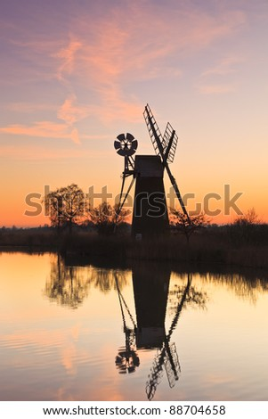Pink clouds and reflection of Turf Fen wind pump at sunset.