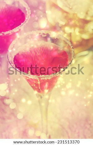 Pink cocktail with salt over shiny lights - stock photo