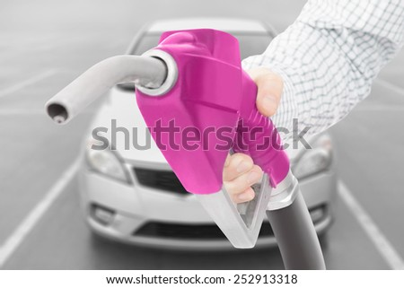 Pink color fuel pump gun in hand with car on background - stock photo