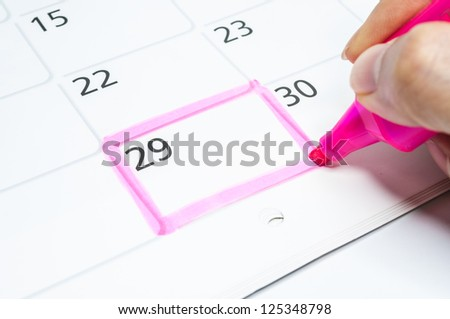 Pink color. Mark on the calendar at 29. - stock photo