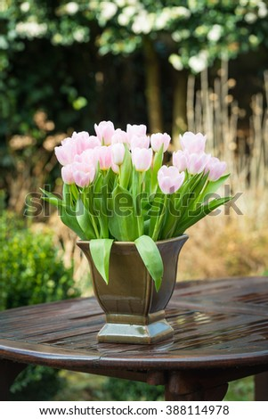 Pink colored tulip flowers in a brown green vase on a wet wooden garden table. It has just rained on an early morning in the winter season. - stock photo