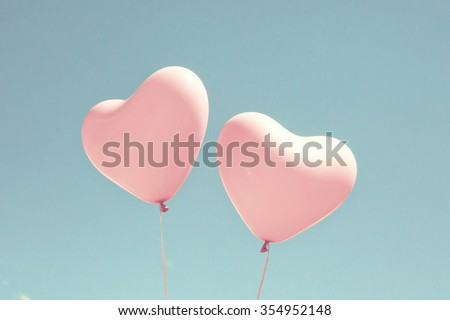 Pink coral heart balloons over a pastel blue sky