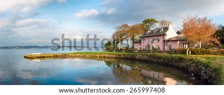 Pink cottage on the South West Coast path as it passes through Empacombe Quay at Mount Edgcumbe in Cornwall - stock photo