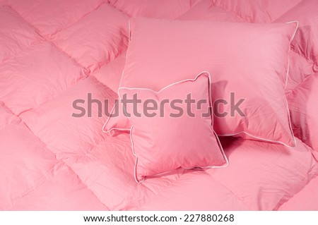 Pink cotton fluff two pillows on big duvet without cover, eiderdown filled with fluff or feathers. Horizontal orientation, nobody.
