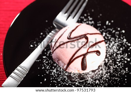 Pink cream cake on a black plate with a fork on red background - stock photo