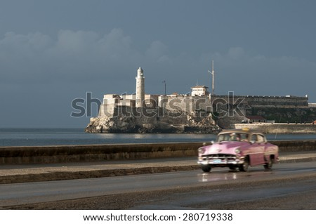 Pink Cuban taxi drives in front of el Morro lighhouse along the Malecon in Central Havana - stock photo