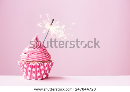 Pink cupcake decorated with a sparkler - stock photo