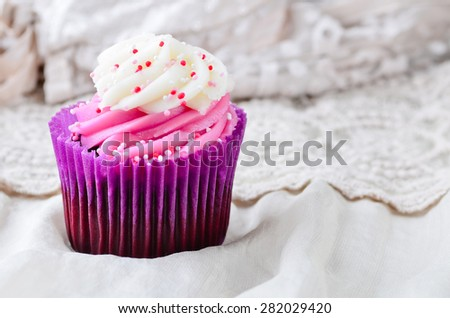 Pink Cupcake iced with sprinkles. - stock photo