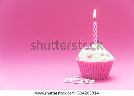 pink cupcake with candle and pink background - stock photo