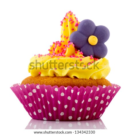 Pink cupcake with flower and yellow butter cream isolated over white background