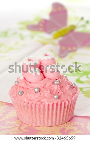Pink cupcake with little sugar booties for girls birth or christening