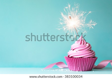 Pink cupcake with sparkler - stock photo