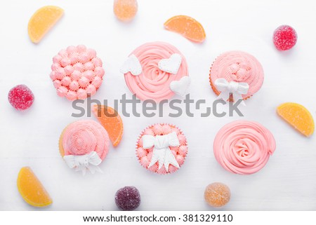 Pink cupcakes on a light background, top view, pink cream, paste, marmalade, candies - stock photo