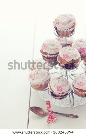 Pink cupcakes on cupcake stand on wooden background - stock photo
