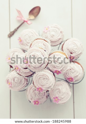 Pink cupcakes on cupcake stand on wooden background, top view - stock photo