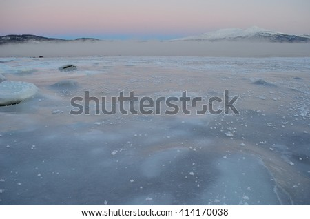 pink dawn sky over snowy mountain and icy fjord with thick ice fog floating over the surface - stock photo
