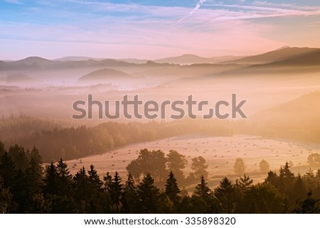 Pink daybreak in fall hilly countryside. Autumn misty morning in a beautiful hills. Peaks of hills are sticking out from fog