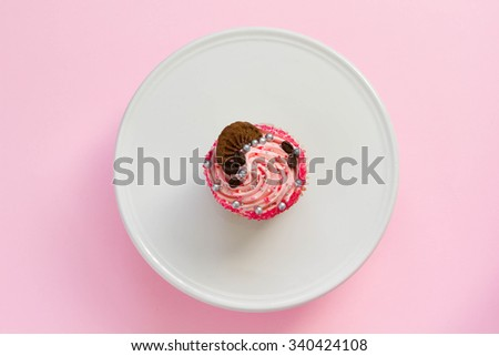 Pink decorated cupcake on white and pink background, top view, minimal style. - stock photo