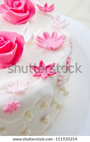 Pink decorative fondant flowers on a white cake.