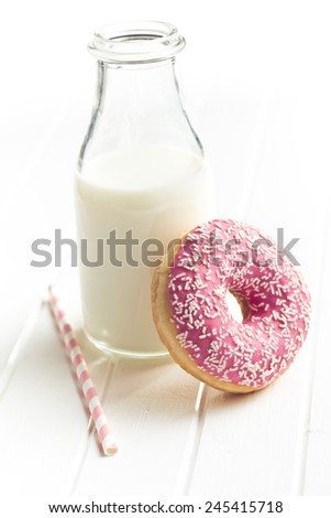 pink donut and milk on kitchen table - stock photo