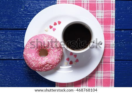 Pink donut with cup of hot coffee on a blue wooden table, top view
