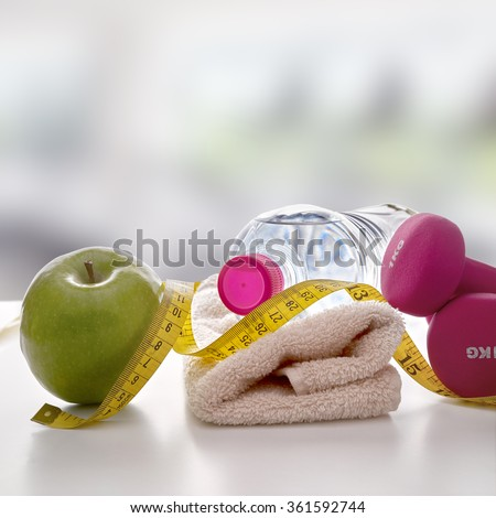 Pink dumbbells with apple, mineral water bottle, towel and tape measure on white table and gym background. Concept health, diet and sports. Square composition. Front view - stock photo
