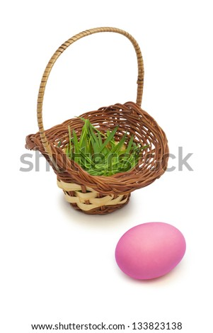 Pink easter egg and basket full of grass