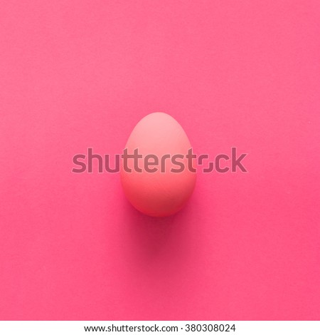 Pink egg on pink background - top view - stock photo
