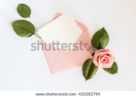 Pink envelop with white card and rose. Flat lay, top view. - stock photo