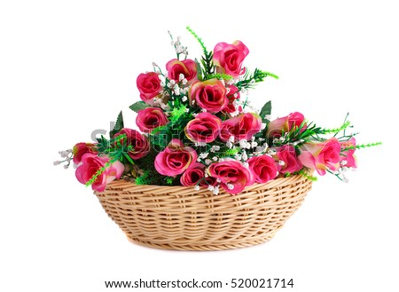 Pink fabric roses in wicker basket isolated on white background.