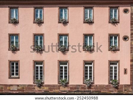 "Pink facade of a building with windows and flowers in pots in the historic district ""Petite France"" in Strasbourg, Alsace, France - stock photo"