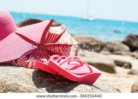 Pink Flip Flops Bag Starfish on Stone Beach Coastline Sea Relax Summer Holiday Concept - stock photo