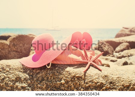 Pink Flip Flops Bag Starfish on Stone Beach Coastline Sea Relax Summer Holiday Concept Toned - stock photo