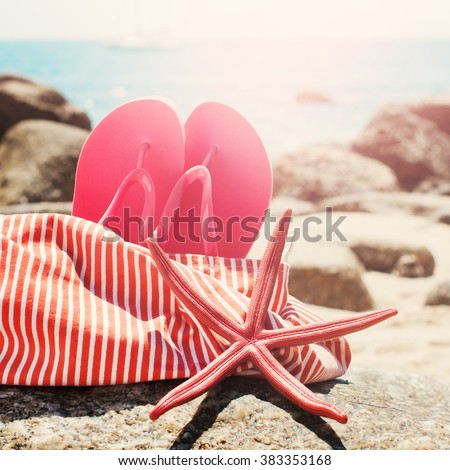 Pink Flip Flops Bag Starfish on Stone Beach Summer Holiday Concept Toned - stock photo