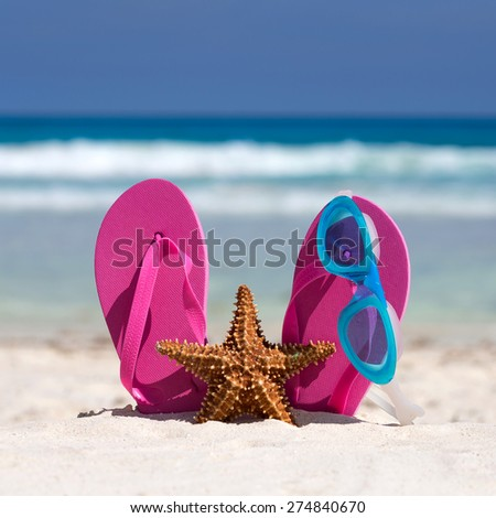 Pink flip flops, swimming glasses and starfish on white sandy beach. Summer vacation concept