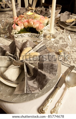 Pink flower arrangement on a grey tone fancy christmas table with antique cutlery - stock photo