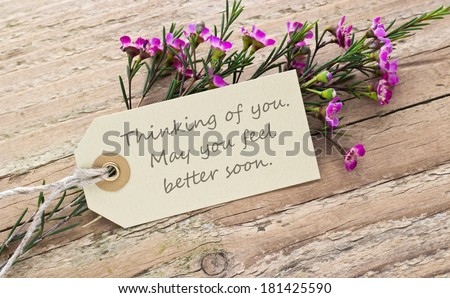 pink flower on a wooden board with card/thinking of you. May you feel better soon./english - stock photo
