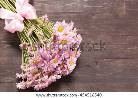 Pink flowers are on the wooden background with ribbon.