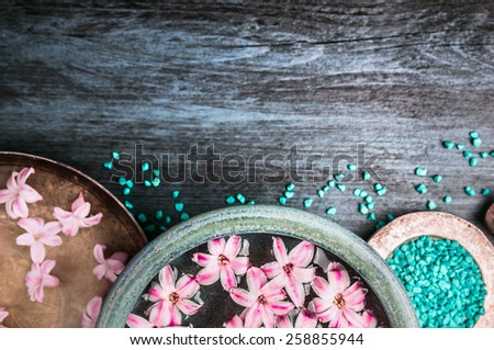 Pink flowers in bowls with water and blue sea salt on wooden table, wellness background, top view, place for text - stock photo