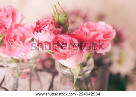 Pink flowers in glass bottles in metal basket. Vintage decor concept - stock photo