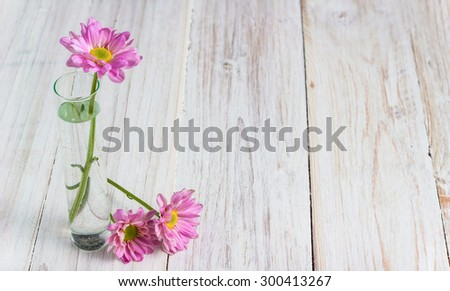 pink flowers in glass on white wooden table.
