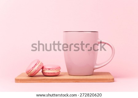 Pink french macaroons and pink cup of coffee lying on wooden board, on pink background - stock photo