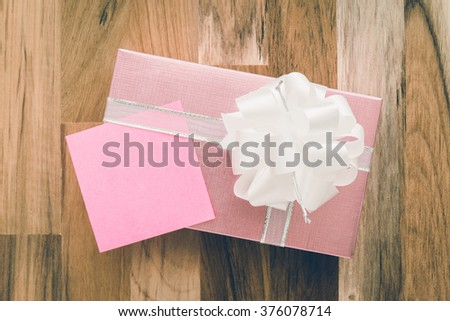 Pink gift box and paper note on wooden background - Vintage filter effect - stock photo
