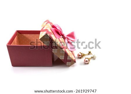 Pink gift box tied with a pink ribbon earrings pink on a white background.
