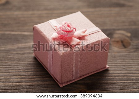 Pink gift box with bow on a wooden table, closeup, selective focus - stock photo