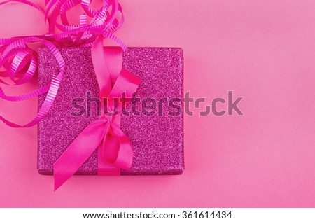 Pink gift box with ribbon and bow on a pink background - stock photo