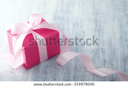 Pink gift box with ribbon on white painted wood background - stock photo